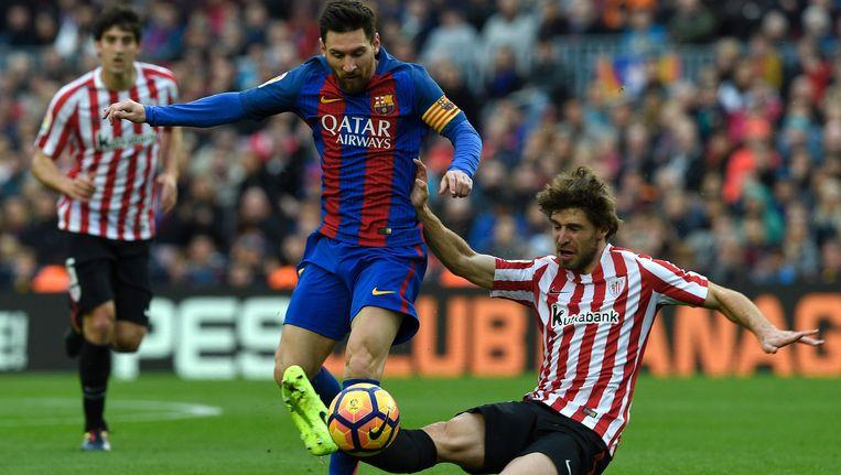 Yeray Alvarez zet een tackle in op Lionel Messi. Beeld AFP