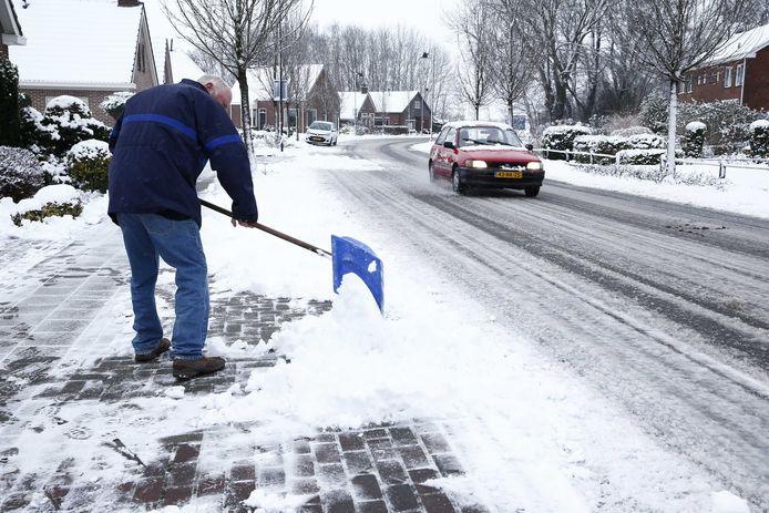 2016-01-16 10:40:09 Een man veegt, vrijwillig, de sneeuw van de stoep voor zijn huis. Gemeenten kunnen inwoners niet dwingen, maar er bestaat wel zoiets als een 'morele plicht'.  SANP VINCENT JANNINK