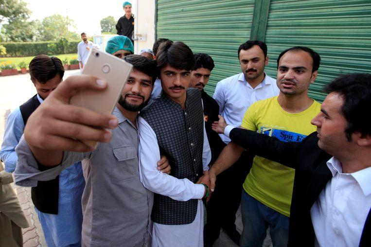 Mensen houden Arshad Khan tegen voor een foto. Beeld REUTERS