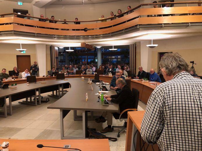Huurder Jan Rison spreekt de commissie toe tegenover een bomvolle raadszaal met ontevreden huurders.