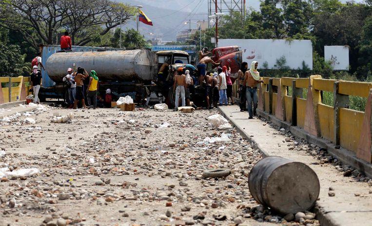 Venezolanen proberen een blokkade op de grens met Colombia weg te werken. Konvooien met hulpgoederen werden dit weekend tegengehouden door troepen van president Nicolas Maduro, waarna protesten uitbraken.  Beeld AP