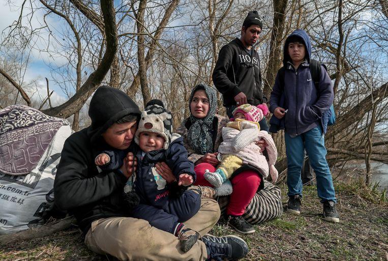 Een groep migranten op de oever van de Meric (Evros) rivier aan de Turks-Griekse grens bij Edirne, aan de Turkse kant. Beeld EPA