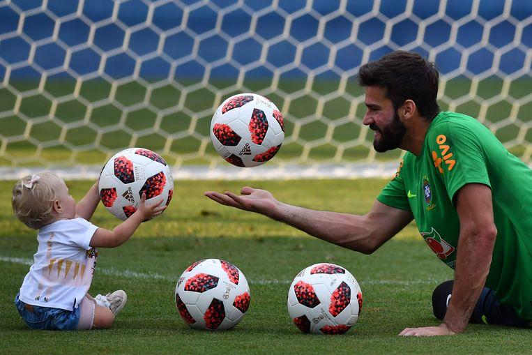 De Braziliaanse doelman Alisson Becker speelt met zijn dochtertje op training. Beeld AFP