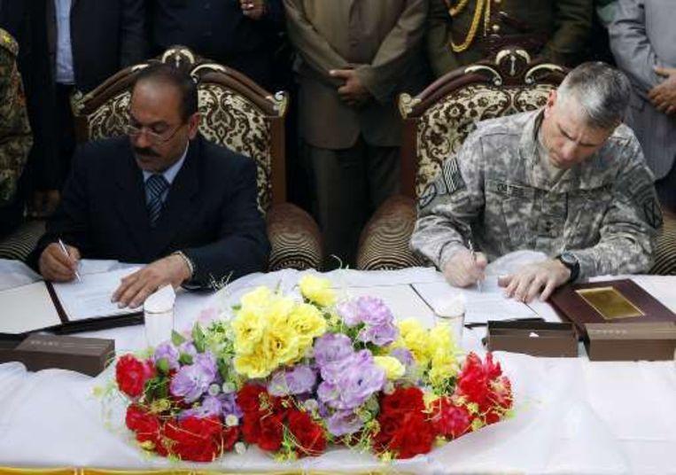 De gouverneur van Babil en Amerikaans generaal Michael Oates ondertekenen de overdracht. Beeld UNKNOWN