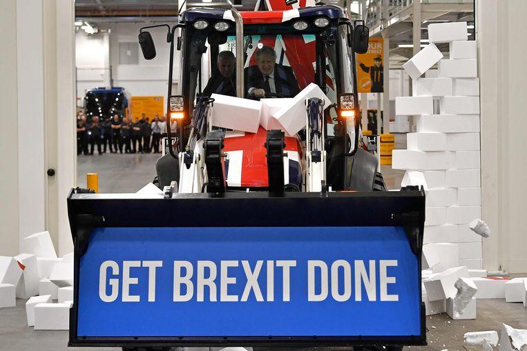 De Britse premier Boris Johnson rijdt in december 2019 door een nep-muur met een pro-Brexit-boodschap.  Beeld AFP