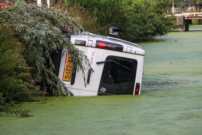 Het busje raakte op zijn kant en valt het water in.