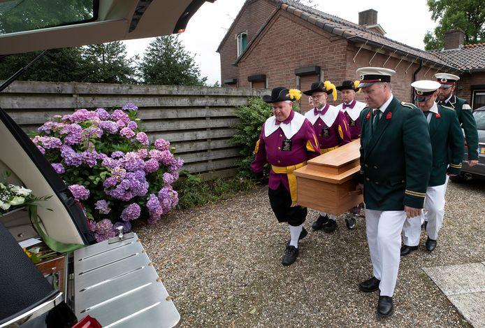 Leden van het schuttersgilde Sint Joris dragen de kist die gemaakt is van oude kerkbanken.