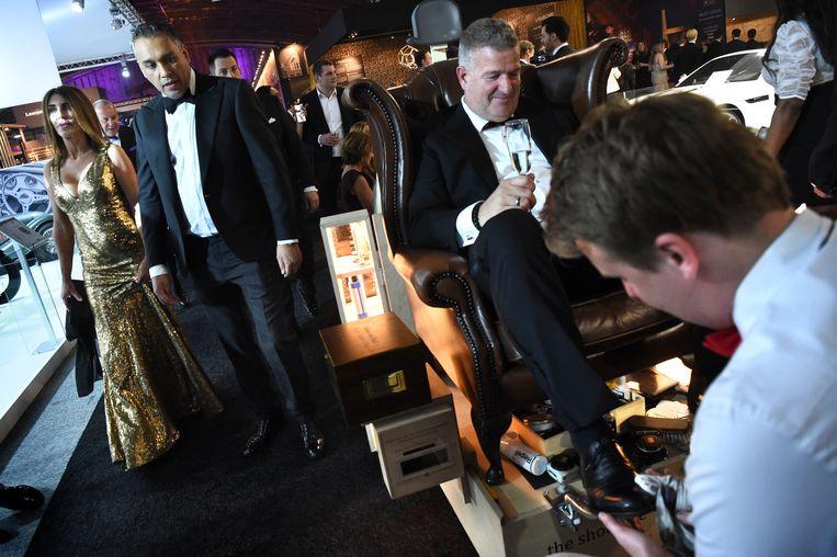 Masters of LXRY in de Amsterdamse Rai, 2018, waar veel miljonairs komen; een man laat zijn schoenen poetsen.  Beeld Marcel van den Bergh