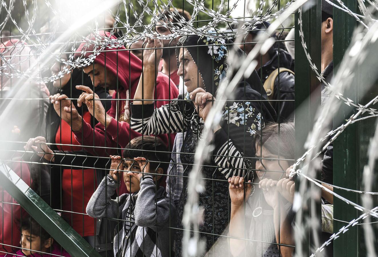 Vluchtelingen die voor een dichte Hongaarse grens staan. De nieuwe route leidt de vluchtelingen langs mijnenvelden in Kroatië.