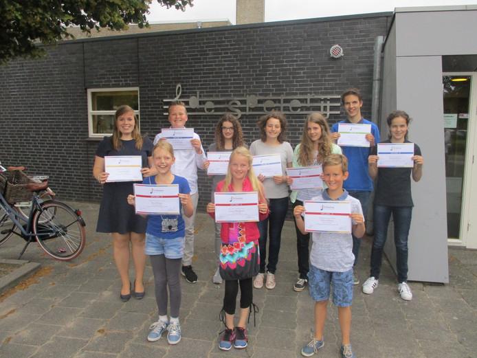 Tien van de in de totaal achttien leerlingen poseren trots met hun zojuist behaalde diploma.