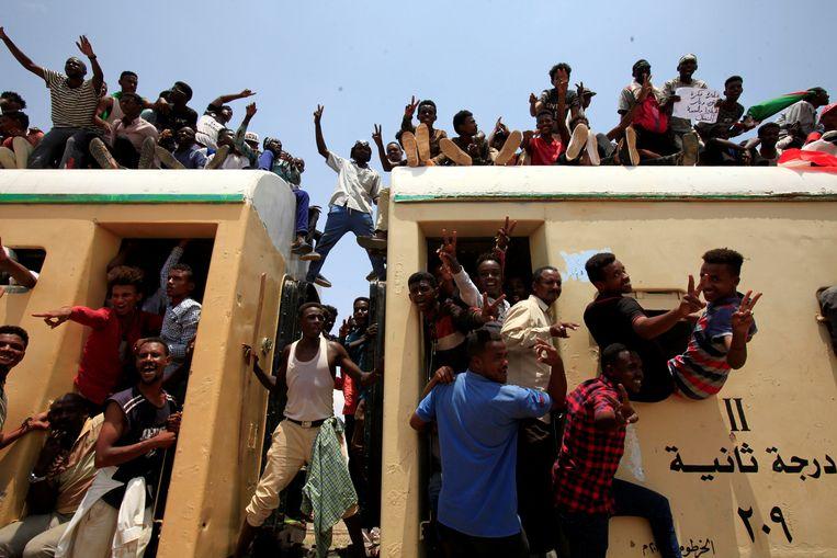 Treinreizigers in Soedan geven uiting aan hun vreugde over het akkoord over de machtsdeling tussen militairen en burgers.  Beeld REUTERS