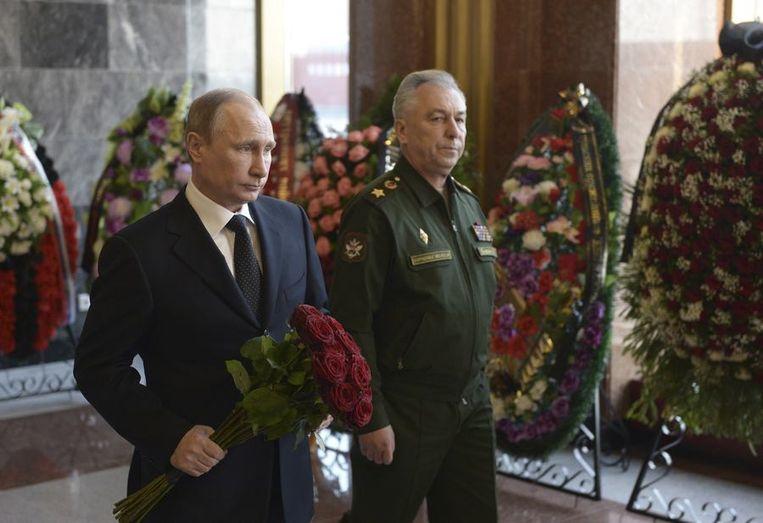President van Rusland, Vladimir Poetin, houdt bloemen vast terwijl hij naar de kist van Michail Kalasjnikov loopt. Beeld reuters