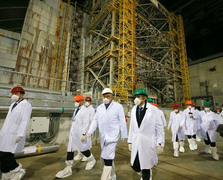 Onderzoekers wandelen langs het omhulsel over de ontplofte kernreactor. Beeld AP