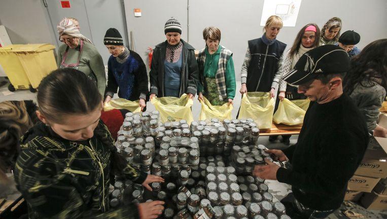 Medewerkers van het Rinat Achmetov-fonds stellen voedselpakketten samen in het verlaten stadion van de voetbalclub Sjachtar Donetsk, waarvan Achmetov de eigenaar is. De schatrijke zakenman, voorheen de koning van de Donbas, is naar Kiev uitgeweken. Hij onderhoudt echter ook contacten met de rebellen. Beeld REUTERS