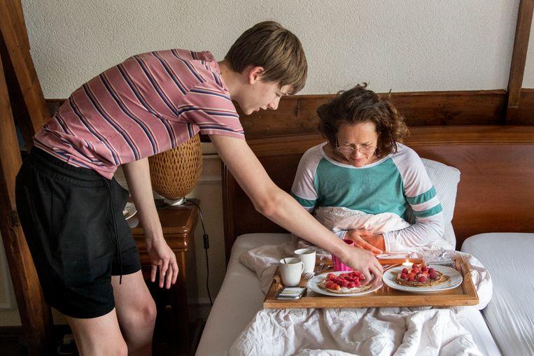 Moeder Petra krijgt van zoon Sam (14 jaar) een ontbijt op bed tijdens moederdag. Pannenkoekjes met frambozen en koffie. Beeld Arie Kievit