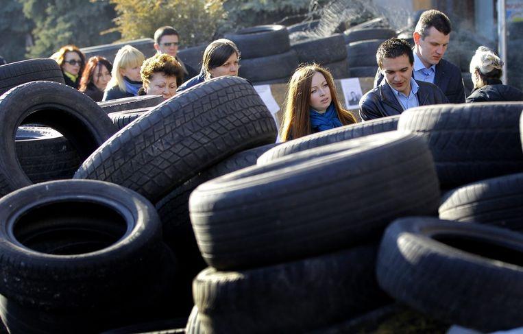 Mensen in Kiev werken zich een weg door de barricades van autobanden bij het Onafhankelijkheidsplein. Beeld epa