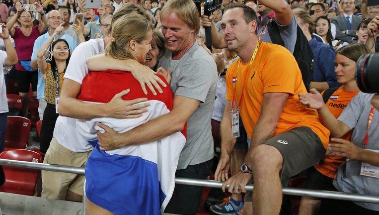 Dafne Schippers direct nadat ze het goud op de 200 meter in de wacht heeft gesleept, vrijdag in Peking. Rechts haar vader. Beeld AP
