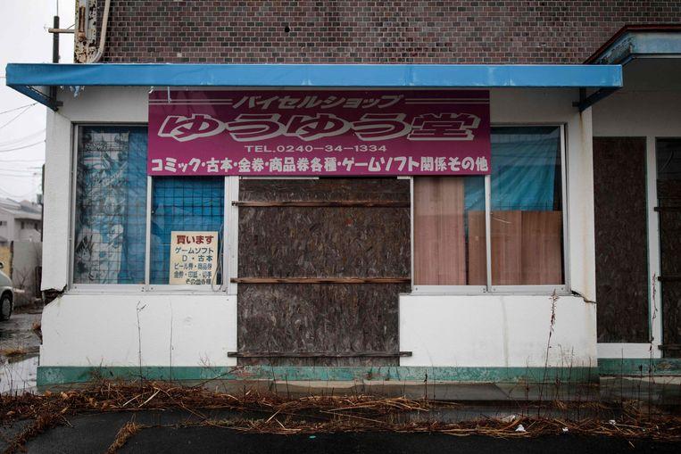 Een verlaten winkel in het stadje Namie, in de buurt van Fukushima. Beeld AFP