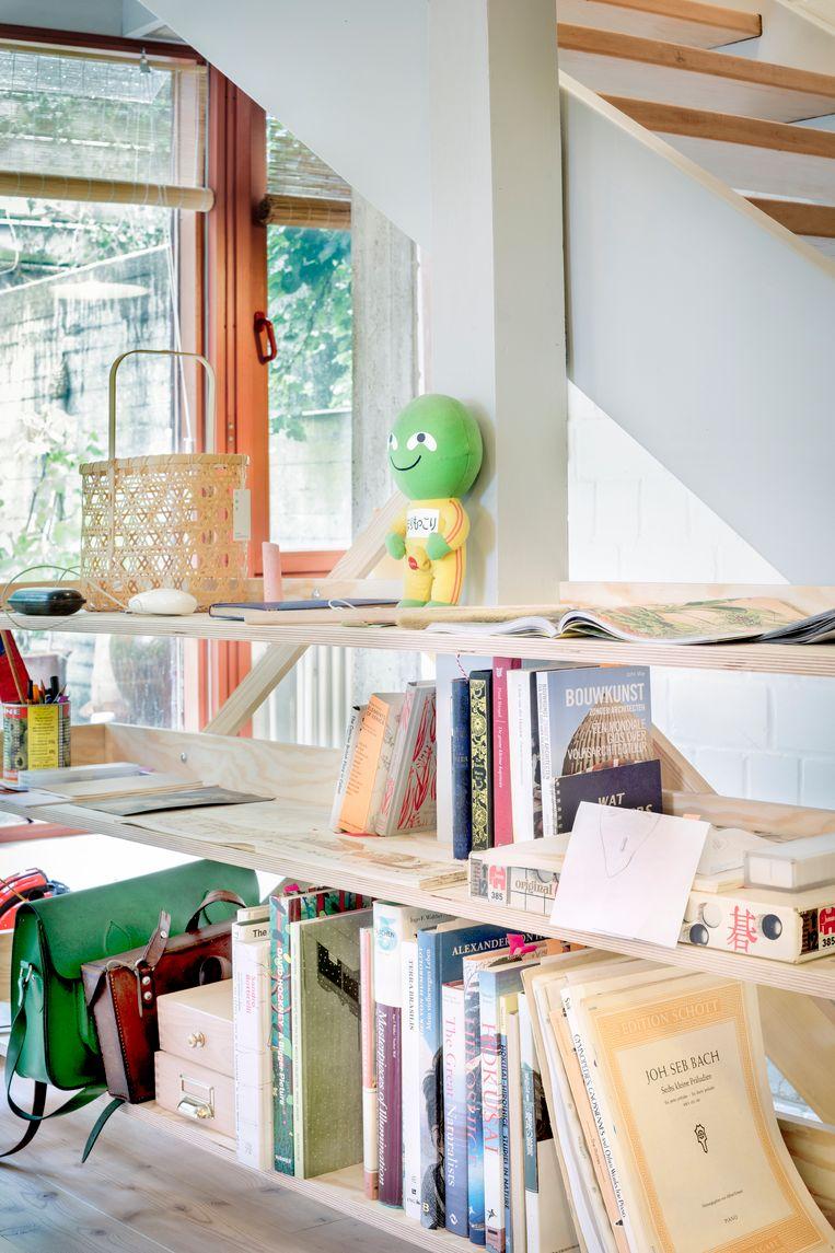 De open schappen, zelf gebouwd uit eenvoudige multiplex, doen niet alleen dienst als boekenkast, maar ook als afscheiding met de trap.   Beeld Marleen Sleeuwits