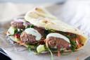 Gezonde falafel met pitabrood, gemengde groenten en yoghurtsaus.