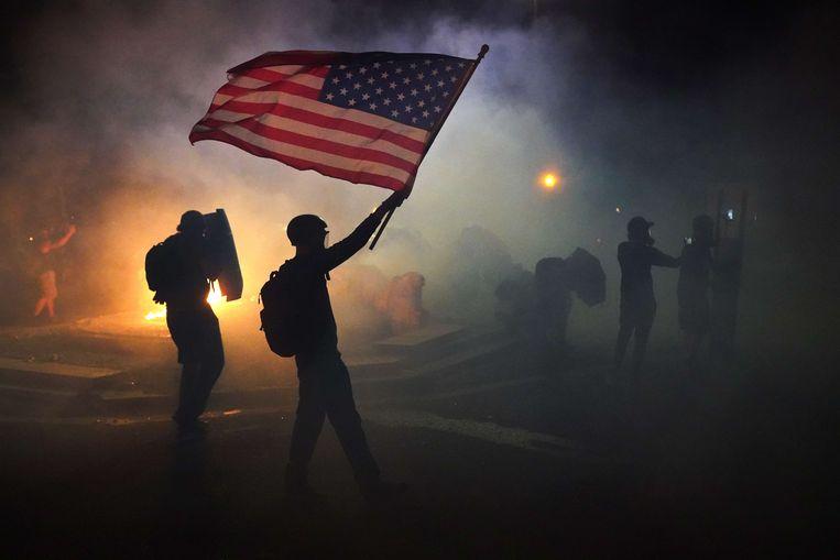 Een demonstrant loopt, gewapend met een vlag, door een zee van traangas.  Beeld AFP