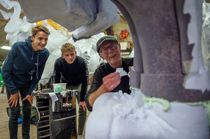 Emar Trompert (links) kijkt samen met Levi van der Schot (midden) toe naar de bouwkunsten van Piet Theunis tijdens de 'excursie' naar de loods van De Vlaojestaampers.