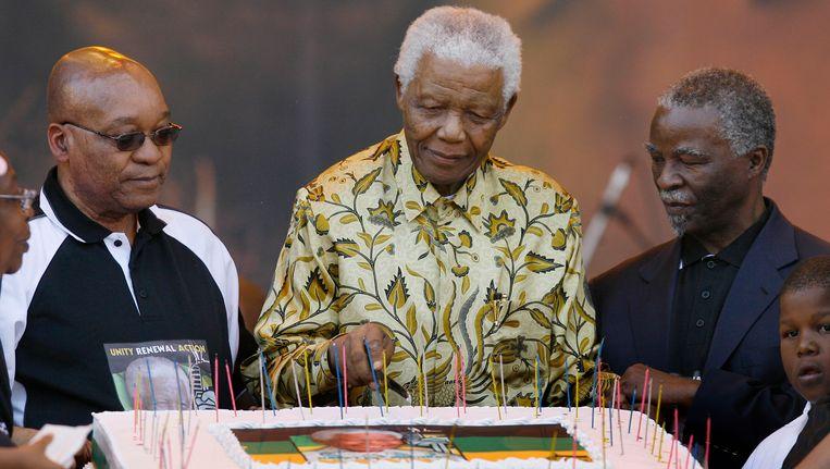 Nelson Mandela snijdt de taart aan ter ere van zijn 90ste verjaardag, in 2008. Beeld AP
