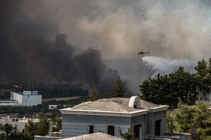Een helikopter laat zijn lading water vallen tijdens het blussen in het gebied van Varympompi.