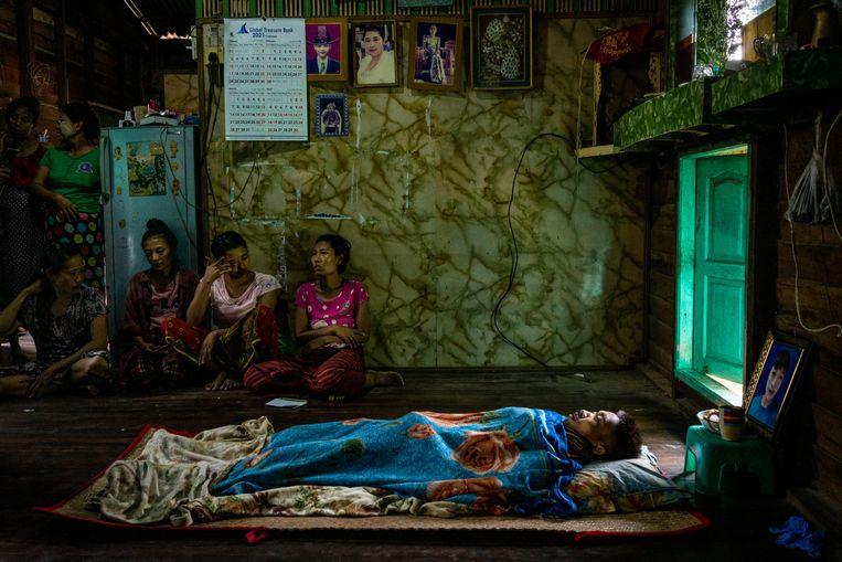 Rouwende vrouwen zitten bij het lichaam van de negentienjarige Kyaw Htet Aung die werd doodgeschoten door de veiligheidsdienst in Myanmar..  Beeld Getty Images
