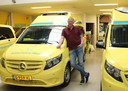 Kees Veldboer tussen de voertuigen van zijn Stichting Ambulance Wens.