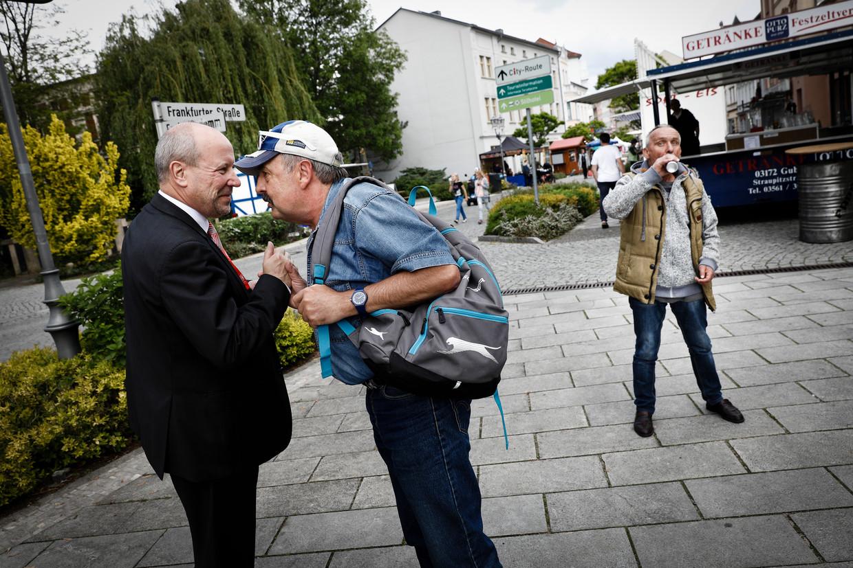 Fred Mahro (links), de burgemeester van Guben, wordt aangeklampt door een inwoner. Beeld Daniel Rosenthal / de Volkskrant