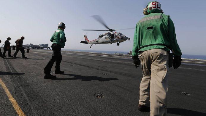 Een Amerikaanse gevechtshelikopter keert terug naar het vliegdekschip USS George H.W. Bush na een missie in Irak.