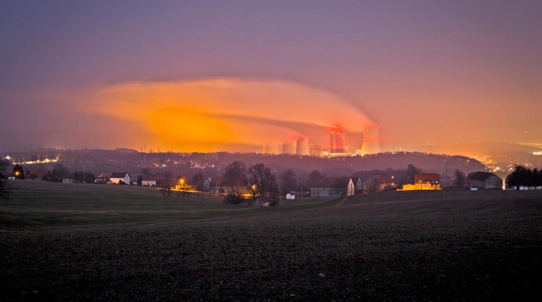 Uitzicht vanuit Duitsland op de verlichte koeltorens van de Turow-energiecentrale in Bogytynia, Polen. Beeld Getty Images