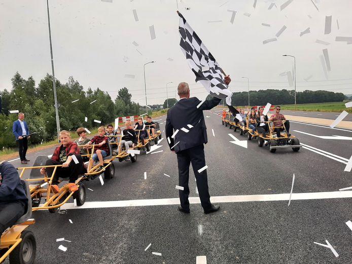 Wethouder Rens Steintjes opent symbolisch de Europaweg door twee skelters met leerlingen van SO De Isselborgh af te vlaggen.
