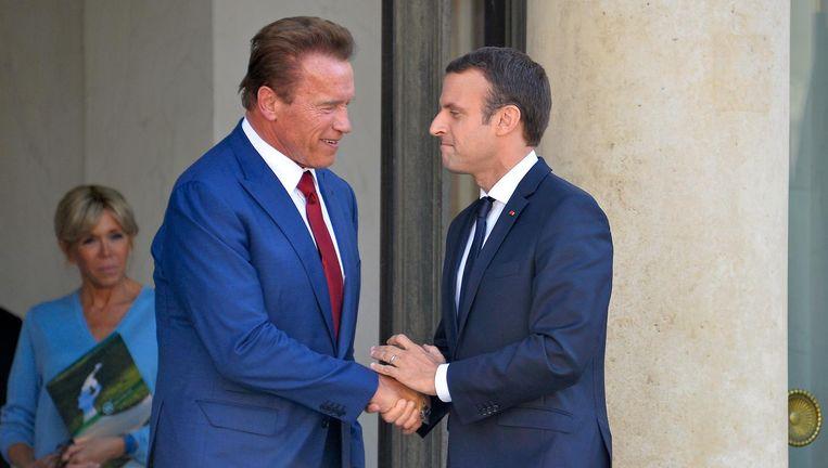 Arnold Schwarzenegger, links, en Emmanuel Macron. Beeld getty