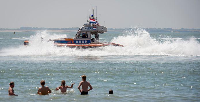Een passerende reddingsboot van de KNRM op het strand in Vlissingen.