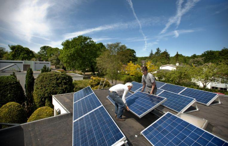 12 mei 2011: ik help Danny Bolten bij het plaatsen van het laatste zonnepaneel. De stroom kan gaan stromen. Beeld Olaf Kraak