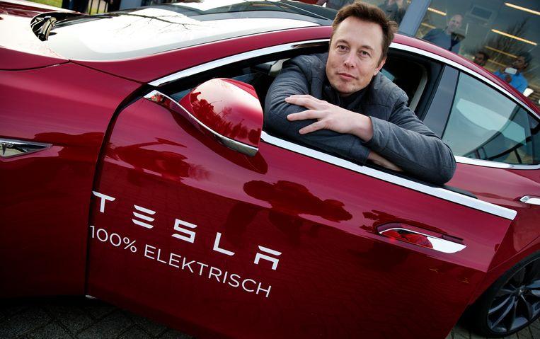Musk poseert met een Tesla tijdens een bezoek aan Nederland Beeld ANP