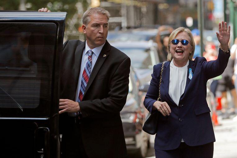 Hillary Clinton zwaait naar het publiek bij het verlaten van het huis van haar dochter Chelsea, waar ze vorig weekend even uitrustte nadat ze onwel werd. Beeld REUTERS
