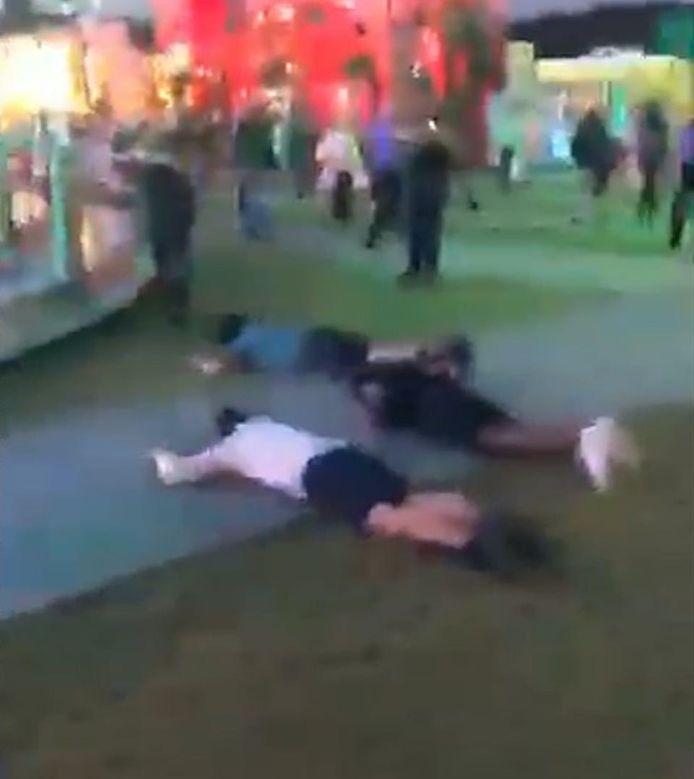 De jongens liggen op de grond, midden op een drukke kermis.