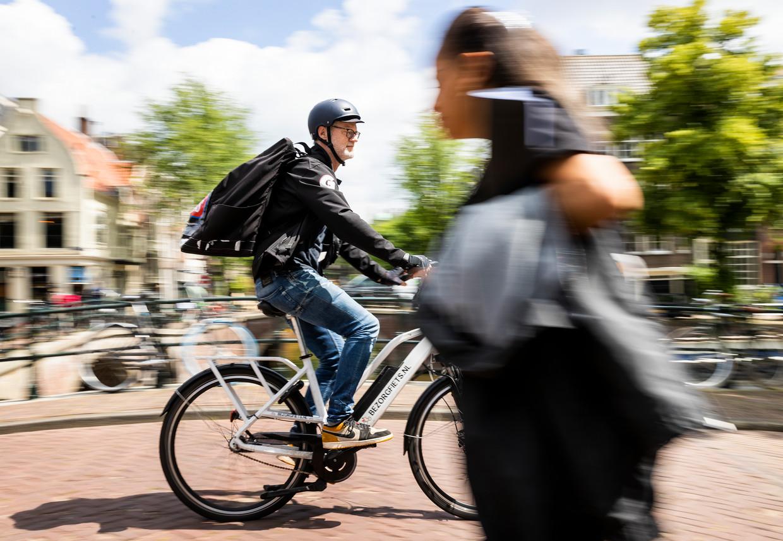 Journalist Jeroen van Bergeijk fietst door Amsterdam, boodschappentas op de rug. Beeld Jiri Büller / de Volkskrant